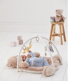 The Teddy's Toy box  Playmat is a soft, comfortable and luxurious padded bear-shaped playmat with two arches and five different detachable toys for your baby to watch and touch. The playmat can be used without arches as your little one gets older.