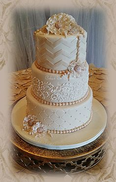 Hey hey Paula!  Ivory flowers, ruffles, pearls, piping and chevron for the smart chic wedding cake.