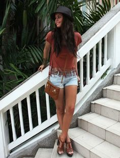 Short shorts, heeled sandals, cute little bag, fringed tee, and fedora with awesome hair.
