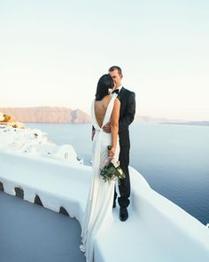 """In terms of backdrop and back-of-dress..... Does it get any more epic than this?! Nancy wore @badgleymischka for her Santorini elopement to Joe …"""