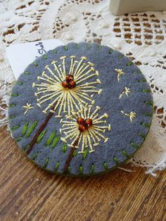 Dandelion. The flower is embroidered on felt with straight stitches and few beads have been added to depict the center of the flower.