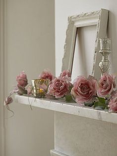 roses, roses, roses on a white mantle with mercury candlestick and cup. White picture frame. Love