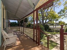 Verandah for a Queenslander home with bullnose roofing, timber decking and picturesque iron work as handrails. Beautiful! #handrails #ironwork #bullnoseroof #deck #verandah