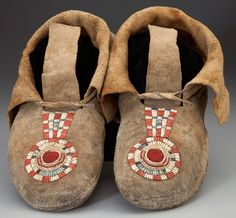 "AN EARLY PAIR OF INTERMONTANE QUILLED BUFFALO HIDE MOCCASINS c. 1850.  each ""keyhole"" with circular panel of red wool trade cloth, enclosed within an elevated spiral of horsehair, wrapped in natural, blue and red-dyed porcupine quills, long hide ties and soft soles. Lengths: 11 inches. ""Heritage Auctions. 2009 September American Indian Art Auction #6029"""