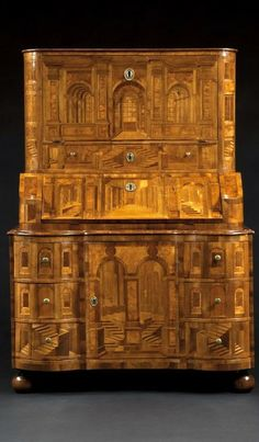 AN UNUSUAL BUREAU CABINET PROFUSELY DECORATED WITH ARCHITECTURAL PERSPECTIVE MARQUETRY