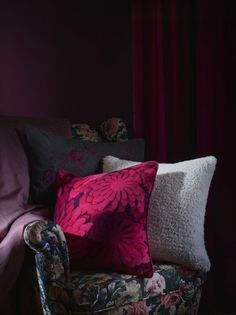 Patterned cushions on a dark floral armchair against a dark red backdrop. Patterned cushions on a dark floral armchair against a dark red backdrop.
