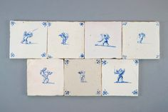 Een leuke set van 7 blauw-witte Delftse tegels met amortjes, 17/18e eeuw