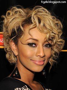 """W katalogach fryzur dominują zazwyczaj modne uczesania z włosów prostych, bo lepiej widać na nich misterne cięcia. Tymczasem kręcone włosy też są bardzo sexy! Wyglądają niebanalnie, """"pracują"""" z każdym ruchem głowy i zapewniają ładną objętość.Na zdjęciu ciemny blonde (bronde) i asymetryczna kręcona fryzurka z delikatnie podpiętym bokiem. Jeśli myślicie, że kręcone włosy i grzywka to kiepski pomysł, popatrzcie jak rewelacyjnie wygląda tutaj! :) Loki także fajnie wyglądają w towarzystwie ..."""