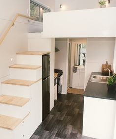 The kitchen is equipped with laminate countertops, freestanding range, dishwasher, and refrigerator under the stairs.