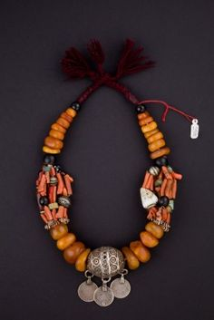 Necklace Morocco Beginning 1900 - The necklace is composed of large grains of amber, coral strands of logs, glass and shells, the center holds a large oval pearl silver tagemout, and spaces designed by the wire in silver bears traces of yellow and green enamels, to which three coins are h