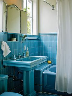 "Instead of replacing all the vintage tiles and the bathtub, these homeowners restored their bright blue bathroom to create a vintage chic look.  I do like this one very much....we are too interested in tossing out the old and bringing in the new....I don't want a ""today's world, cookie cutter bathroom""....this one has some personality!"