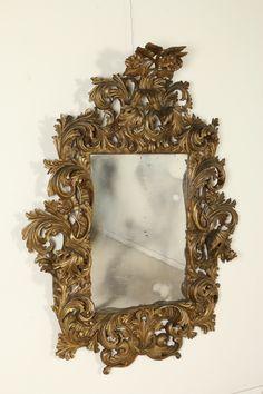 Importante specchiera con volute e foglie d'acanto accartocciate. Cimasa con girasoli intagliati.