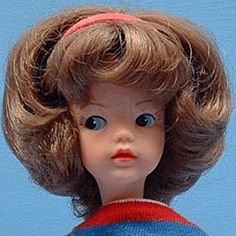 In 1963 Sindy arrives in the UK with wayward short curly hair with a red head band. She was sold wearing a striped jersey top weekenders and wore blue jeans and white sneakers on her feet.