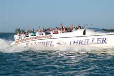 Passengers wave on Sanibel Thriller power super catamaran boat dolphin, wildlife tour Sanibel Island, Florida. Must Do Visitor Guides, MustDo.com