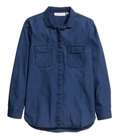 Long-sleeved shirt in soft, washed denim with a narrow collar. Chest pockets with flap, concealed fastening at front, and gently rounded hem. Slightly longer at back.