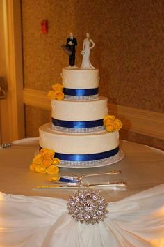 Royal blue and bling ribbons along with double hearts and bright yellow roses. www.mitchels.ca #wedding #weddingcakes #flowers #roses #royalblue