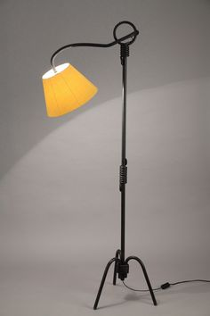Black lacquered iron tripod lampstand after a model by Jean Royère, with an adjustable arm of light (five positions). Yellow new lampshade.