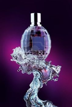 Perfume bottle on water splash. Glass perfume bottle on a water splash in shades of purple and black. Stock Photo