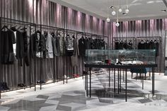Solidity of four different types of marble at the shop window, cashier and flooring areas matching with softness of grayish purple curtain in velvet as a background, have created a balance between masculine and feminine in the space.