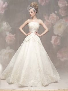 A subtle crossover at the waist creates a flattering effect on this strapless, floral-embroidered ballgown.