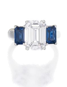 PLATINUM, DIAMOND AND SAPPHIRE RING  Estimate: 70,000 - 90,000 USD   Centered by an emerald-cut diamond weighing 4.03 carats, flanked by two emerald-cut sapphires weighing approximately 2.10 carats, size 6¾, fitted with inner sizing bar.