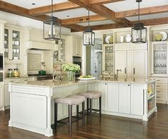 A Trio Of Oversize Lanterns Ground This Cream Color Kitchen. Exposed  Ceiling Beams And