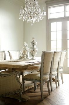 Perfect contrast.  Beautiful, calm, neutral.  Natural, rough with sparkle. Trestle table, nailhead trim chairs, floor, mercury glass crystal chandelier.  Dream Dining Room.