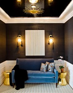 Gold stools as end tables, dark walls and Blue velvet sofa