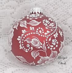 Margot Clark created this red glass ornament with a White 3D floral texture painted design with added rhinestone bling. Each ornament created is a one-of-a-kind. The texture medium and paint brush I use to paint the ornaments were both created to my specifications. My signature M is located on the bottom of the ornament. Gift boxed. Measures 3 x 3 1/2 Ornament weight is 2 ounces.