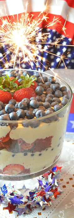White Chocolate Mousse Holiday Trifle~ A Fourth of July Holiday Dessert that fits right in with the parades, parties and fireworks! Made with red velvet cake, white chocolate mousse, strawberries and blueberries. Impress your party guests and get them ready for fireworks when you present this dish at the end of your meal.