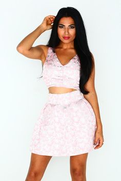 The Lilly Two Piece Pink  $70.00  Adorable yet elegant two piece. It features skirt metallic and pink flower design through out, high waist. Exposed zip closure at back, unlined.