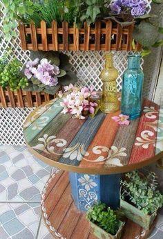 touret bois avec un plateau à planches multicolores et motifs floraux, aménagement jardin exterieur, fleurs et plantes vertes
