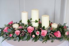 Top table arrangement with roses, spray roses, wax flower, eucalyptus and ivy.  Church pillar candles of different heights.  Liberty Blooms.