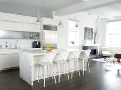 White cabinets and a white marble island make this open kitchen space feel open and airy. A white-on-white scheme creates the illusion of more space, making this color perfect for small abodes.