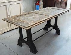 Tavolo in stile industriale-chic con base in ghisa e piano realizzato con una porta antica laccata