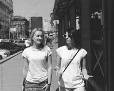 Two positive girls on the street in the city talking and having fun. Black and white film photo