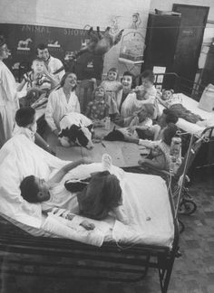 """""""A room full of children, nurses and animals watching as a ferret is crawling across the high-wire as one of the hospital's methods of using therapy with animals."""" September 1956: Francis Miller"""