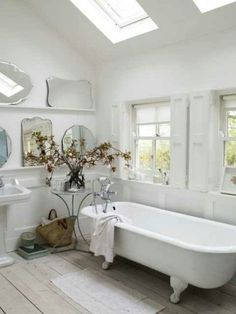 Skylights add natural light to this all white bathroom.