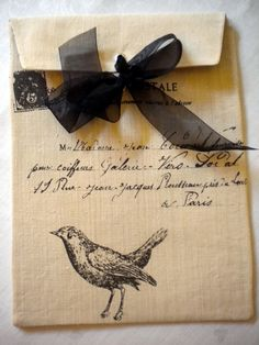 kraft paper envelope with black ribbon, French script, and stamped bird