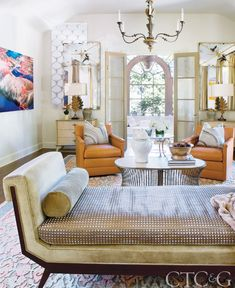 Rinfret chose an armless daybed from Baker Furniture for gatherings of many people in the living room. Formations chandelier is through Holly Hunt. Orange swivel leather armchairs are from Lee Industries. The area rug is from Beauvais Carpets.