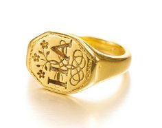 "Unusual English gold signet ring with posey, circa 1600. The signet entwines the letters H&A with flowers and the posey engraved on the interior of the shank reads ""when this you see remember me +""."