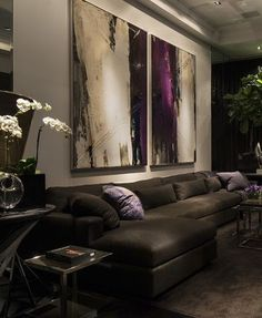Living Room: Cream walls, brown couch with purple cushions + abstract art work
