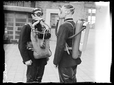 A photograph of two fire fighters wearing breathing equipment, taken in December 1938 by Edward G Malindine for the Daily Herald.        The two members of the London Fire Brigade are shown wearing different types of breathing equipment. The man on the left wears the oxygen-type breathing system used at the time. The man on the right is wearing a French system working using compressed air.