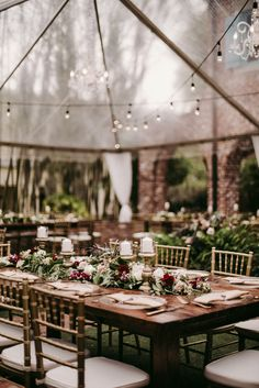 under a clear tent and market lights, varnished farm tables are dressed with lush garlands of lemon leaf, seeded eucalyptus, willow eucalyptus filled with vendela roses, quicksand roses, white majolik spray roses, burgundy snapdragons, burgundy carnations, peach stock and lined with pillar candles on gold pedestals.