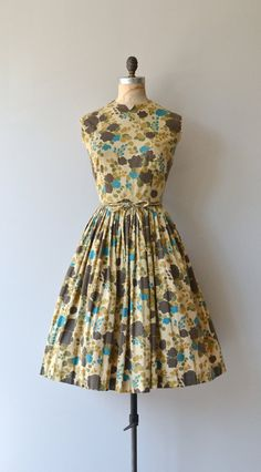Vintage 1950s, early 1960s autumn floral cotton dress with notched collar, sleeveless bodice, fitted waist, full skirt, tie belt and metal zipper. Stacy Ames label