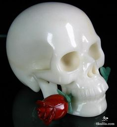 The Eternal Dancer is a lovely white jade crystal skull holding a red jasper and green aventurine rose in her teeth.