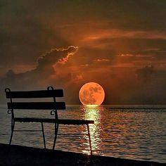 Beautiful moonrise over the water from a park bench.