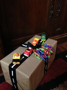 1st birthday party gift wrapping idea. LOVE IT!!!!! - white duck tape - black wide ribbon - cardboard style wrapping paper - fisher price car toys - curly ribbons for fun color