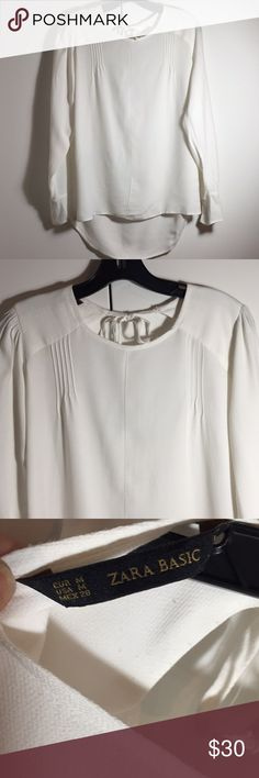 Zara white long sleeved flowy blouse Size medium. EUC. Long sleeve blouse with front pleats and back keyhole neck tie. Slit cuffs with delicate gold button. Slightly longer in back. Zara Tops Blouses