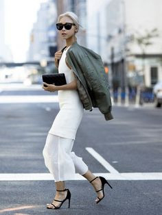 Vanessa Hong of the Haute Pursuit wears a white dress, bomber jacket, strappy heels, and black accessories